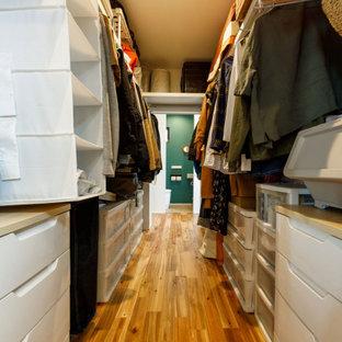 Ejemplo de armario vestidor unisex y papel pintado, industrial, de tamaño medio, con armarios abiertos, puertas de armario blancas, suelo de madera en tonos medios, suelo marrón y papel pintado