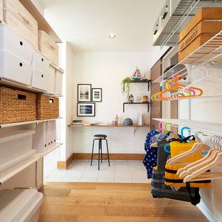 Ispirazione per una cabina armadio unisex moderna di medie dimensioni con parquet chiaro e pavimento beige