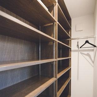 Imagen de armario vestidor unisex, escandinavo, de tamaño medio, con armarios abiertos, puertas de armario de madera en tonos medios y suelo de baldosas de cerámica