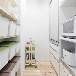 Modelo de armario vestidor de mujer y papel pintado, campestre, con armarios con paneles lisos, puertas de armario blancas, suelo de madera clara y papel pintado