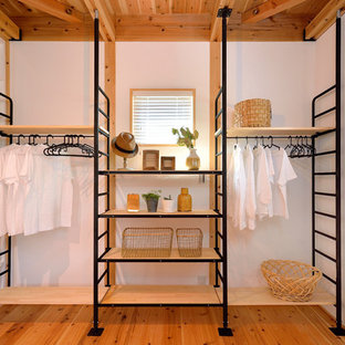 Photo of an industrial built-in wardrobe in Other with medium hardwood floors and brown floor.