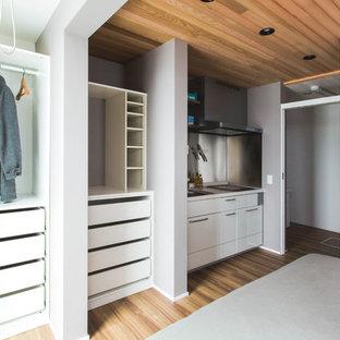 Ejemplo de armario unisex, minimalista, pequeño, con armarios abiertos, puertas de armario blancas y suelo de contrachapado