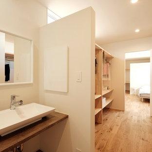 Esempio di una cabina armadio unisex moderna con nessun'anta, ante in legno chiaro, pavimento in legno massello medio e pavimento beige