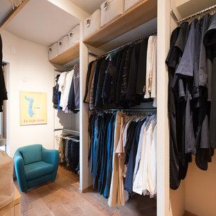 Diseño de armario y vestidor de estilo zen con suelo de madera en tonos medios