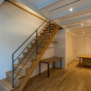 Immagine di una taverna design seminterrata con pareti bianche e pavimento in compensato