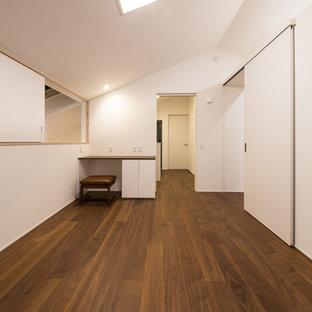 Bild på ett funkis barnrum, med vita väggar, plywoodgolv och brunt golv