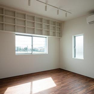 Cette image montre une chambre de fille minimaliste avec un mur blanc, un sol en contreplaqué et un sol marron.