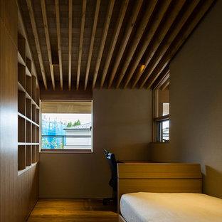 Exempel på ett asiatiskt barnrum kombinerat med skrivbord, med beige väggar och plywoodgolv