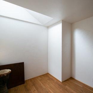 Bild på ett mellanstort funkis könsneutralt barnrum kombinerat med sovrum och för 4-10-åringar, med vita väggar, mellanmörkt trägolv och beiget golv