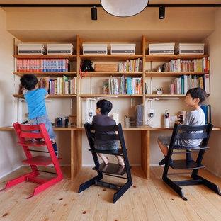 Modelo de habitación infantil unisex de estilo zen con paredes beige, suelo de madera en tonos medios y suelo marrón