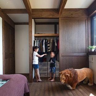 Diseño de habitación infantil unisex asiática con paredes blancas, suelo de madera oscura y suelo marrón