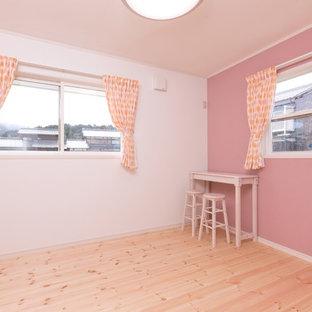 Foto di una cameretta per bambini country con pareti rosa, pavimento in legno massello medio e pavimento beige
