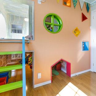 Aménagement d'une chambre d'enfant de 1 à 3 ans contemporaine avec un mur orange et un sol en bois clair.