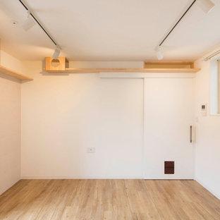 Cette photo montre une chambre d'enfant scandinave de taille moyenne avec un mur blanc, un sol en bois clair, un sol beige, un plafond en papier peint et un mur en parement de brique.