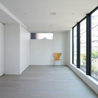Inredning av ett modernt barnrum kombinerat med lekrum, med vita väggar, plywoodgolv och grått golv