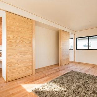 Imagen de dormitorio infantil moderno con paredes blancas, suelo de madera en tonos medios y suelo blanco