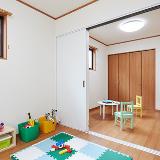 Asian gender-neutral kids' room in Other with white walls and medium hardwood floors.