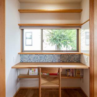 Réalisation d'une chambre neutre de 4 à 10 ans asiatique de taille moyenne avec un bureau, un mur blanc, un sol en bois brun et un sol marron.