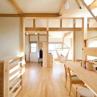 Aménagement d'une grand chambre d'enfant de 4 à 10 ans asiatique avec un mur blanc et un sol en bois brun.