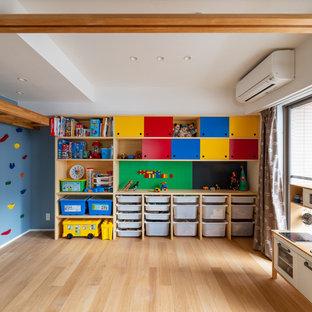 Inredning av ett minimalistiskt mellanstort könsneutralt barnrum kombinerat med lekrum och för 4-10-åringar, med blå väggar, plywoodgolv och brunt golv