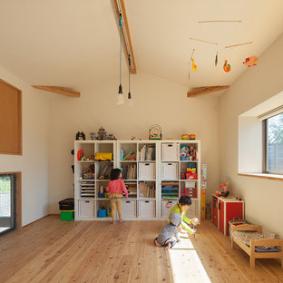 Asian gender-neutral kids' room in Other with light hardwood floors and white walls.
