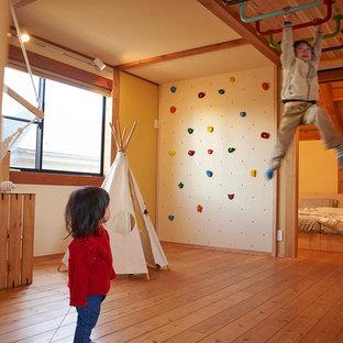 На фото: нейтральная детская с игровой в восточном стиле с белыми стенами, паркетным полом среднего тона и коричневым полом с