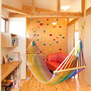 Esempio di una cameretta per bambini da 4 a 10 anni boho chic di medie dimensioni con pareti bianche e pavimento in legno massello medio