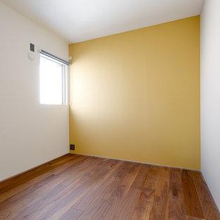 Foto de dormitorio infantil de 1 a 3 años, moderno, con paredes amarillas, suelo de madera oscura y suelo beige
