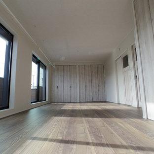 Exempel på ett minimalistiskt barnrum kombinerat med lekrum, med beige väggar, plywoodgolv och brunt golv