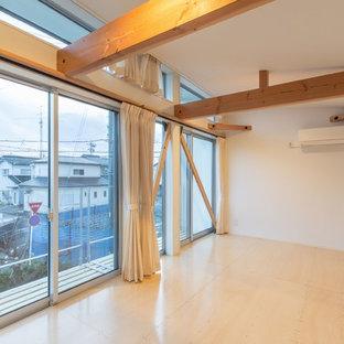 Foto på ett mellanstort orientaliskt barnrum kombinerat med sovrum, med vita väggar, plywoodgolv och beiget golv