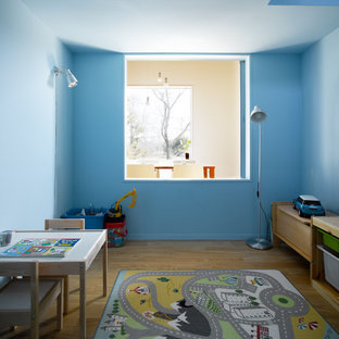 На фото: детская с игровой среднего размера в современном стиле с синими стенами, коричневым полом и полом из фанеры для ребенка от 4 до 10 лет, мальчика