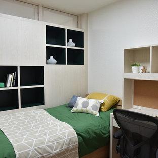 Diseño de dormitorio infantil escandinavo, de tamaño medio, con escritorio, paredes blancas, suelo de contrachapado y suelo marrón