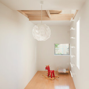 Photo of a scandinavian kids' room in Tokyo with white walls, light hardwood floors and beige floor.