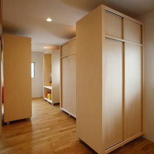 Cette image montre une chambre d'enfant asiatique avec un mur blanc et un sol en bois brun.