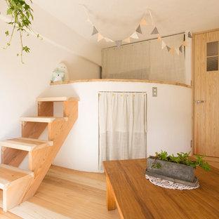 Cette image montre une chambre d'enfant asiatique avec un mur blanc, un sol en bois clair et un sol marron.