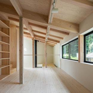 Immagine di una piccola cameretta per bambini etnica con pareti bianche, parquet chiaro, pavimento beige e travi a vista