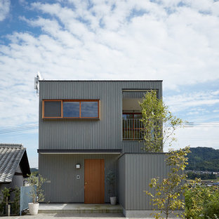 Mid-sized asian grey house exterior in Other with three or more storeys, wood siding, a shed roof and a metal roof.