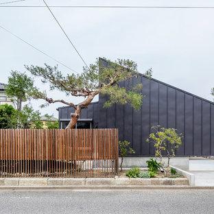 Immagine della facciata di una casa nera scandinava con tetto a una falda