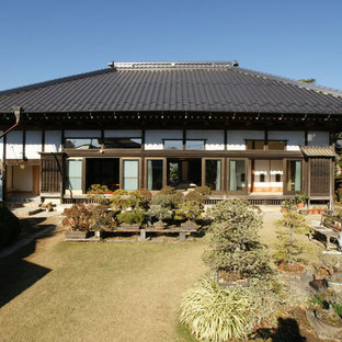 Inspiration for an asian white one-story house exterior remodel in Other with a hip roof and a tile roof