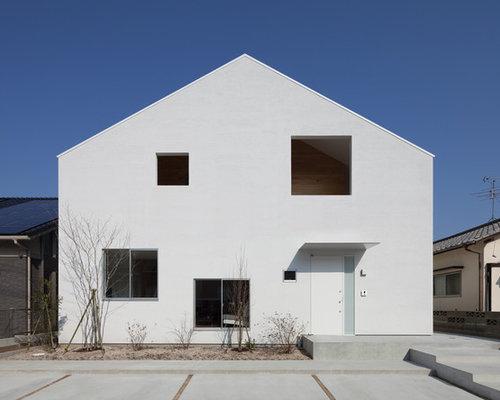 Cette image montre une façade de maison blanche minimaliste avec un toit à deux pans