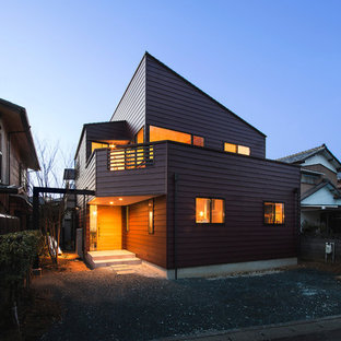 Industrial red two-story house exterior idea in Other with a shed roof and a metal roof