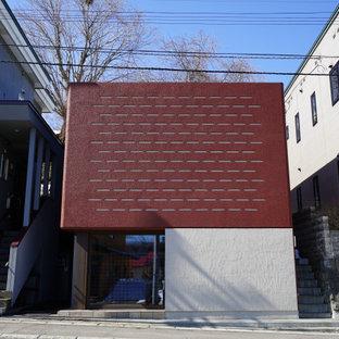 Imagen de fachada roja, minimalista, pequeña, de dos plantas, con revestimiento de hormigón