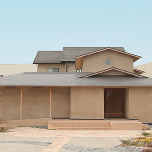 Inspiration for a large asian beige two-story gable roof remodel in Other with a metal roof