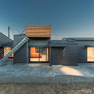 他の地域の巨大なコンテンポラリースタイルのおしゃれな家の外観 (メタルサイディング、グレーの外壁) の写真