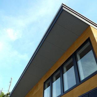 Foto della facciata di una casa unifamiliare piccola gialla moderna a un piano con rivestimento in stucco, tetto a una falda e copertura in metallo o lamiera