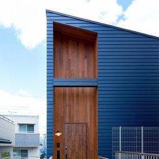 На фото: фасад частного дома синего цвета в современном стиле с односкатной крышей с