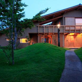 Imagen de fachada beige, asiática, de dos plantas, con tejado a dos aguas