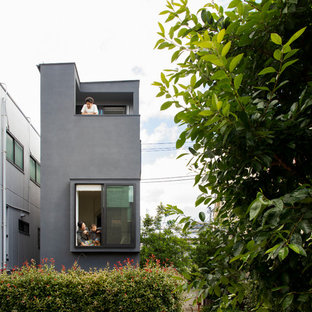 Inspiration for a small eclectic black three-story concrete exterior home remodel in Tokyo with a metal roof