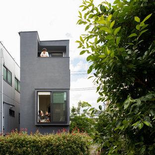 Modelo de fachada de casa negra, ecléctica, pequeña, de tres plantas, con revestimiento de hormigón, tejado plano y tejado de metal