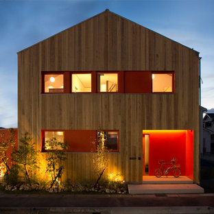 Design ideas for a brown contemporary exterior in Other with wood cladding and a pitched roof.